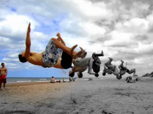 Boys doing a back tuck on the beach